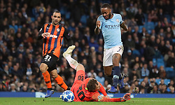 Manchester City's Raheem Sterling (right) and Shakhtar Donetsk's Andriy Pyatov battle for the ball during the UEFA Champions League match at the Etihad Stadium, Manchester.