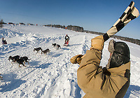 Armand Bolduc gives Jim Blair the checkered flag at the finish line of the final day of the Open Class race at the 86th annual Laconia World Championship Sled Dog Races Sunday afternoon.  (Karen Bobotas/for the Laconia Daily Sun)