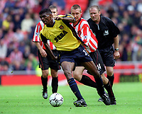Kanu (Arsenal) bursts past Darren Holloway (Sunderland). Sunderland 1:0 Arsenal. FA Premiership,19/8/2000. Credit Colorsport / Stuart MacFarlane.