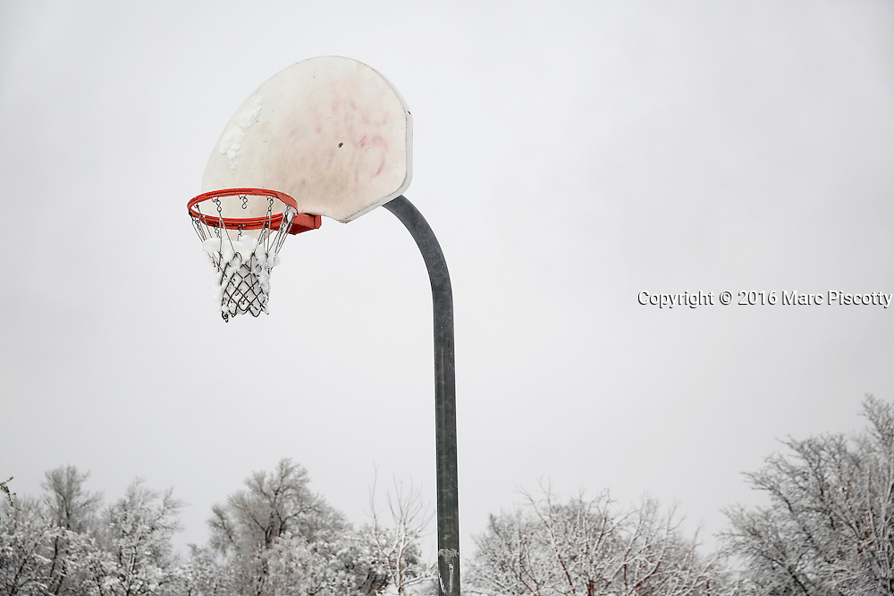 SHOT 3/23/16 5:39:16 PM - A snow covered basketball hoop, rim and net after a late season snow storm in Denver, Co.  (Photo by Marc Piscotty / © 2016)