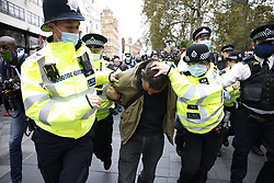 © Licensed to London News Pictures. 17/10/2020. London, UK. Trouble breaks out as police detain a man in Leicester Square as protestors calling for an end to Coronavirus lockdown restrictions march in central London. Other groups who believe that the virus is a hoax and a conspiracy have also joined today's demonstration called the ' March for Freedom'. Photo credit: Peter Macdiarmid/LNP