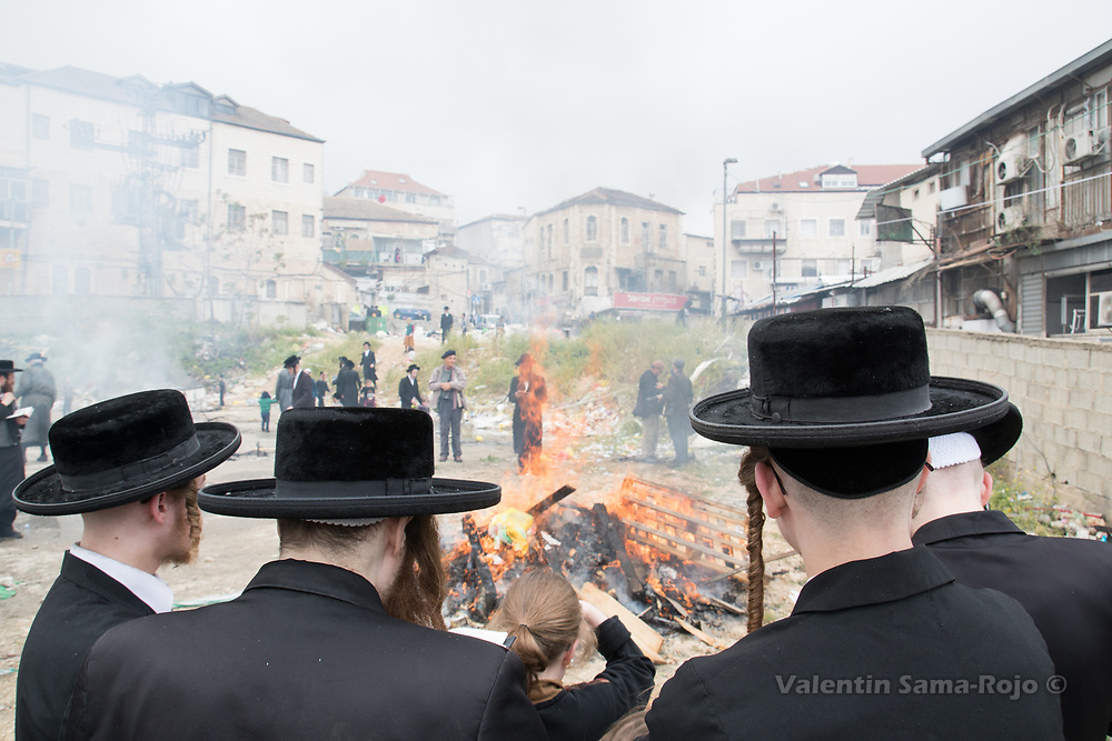 Jerusalem, Israel. 30th March, 2018. A group of people dressing traditional Hasidic cloths in front of a bonfire in Mea Shearim neighborhood during the morning of Pesach. © Valentin Sama-Rojo.