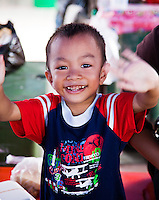 Young boy waving and smiling.