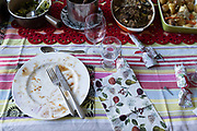 An empty plate, wine glass and a table of food leftovers, the remnants of Christmas excess on Christmas Day, on 25th December 2020 in London, England. Christmas lunch or dinner in the UK is the main meal during the December Christian celebration, when families traditionally come together for the high-protein turkey and high-fibre vegetables - one of the most nutritious meals of the year.