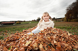 Happy girl in heap of autumn leaves