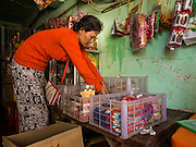 24 FEBRUARY 2015 - PHNOM PENH, CAMBODIA: A shopkeeper sets up her snack stand in a hallway in the White Building. The White Building, the first modern apartment building in Phnom Penh, originally had 468 apartments, and was opened the early 1960s. The project was overseen by Vann Molyvann, the first Cambodian architect educated in France. The building was abandoned during the Khmer Rouge occupation. After the Khmer Rouge were expelled from Phnom Penh in 1979, artists and dancers moved into the White Building. Now about 2,500 people, mostly urban and working poor, live in the building. Ownership of the building is in dispute. No single entity owns the building, some units are owned by their occupants, others units are owned by companies who lease out apartments. Many of the original apartments have been subdivided since the building opened and serve as homes to two or three families. The building has not been renovated since the early 1970s and is in disrepair. Phnom Penh officials have tried to evict the tenants and demolish the building but residents refuse to move out.   PHOTO BY JACK KURTZ