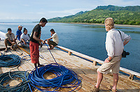 British herpetologist Mark O'Shea stands with other passengers and crew on the deck of a small boat leaving the dock at Beloi, Atauro Island, bound for Dili, Timor-Leste (East Timor)