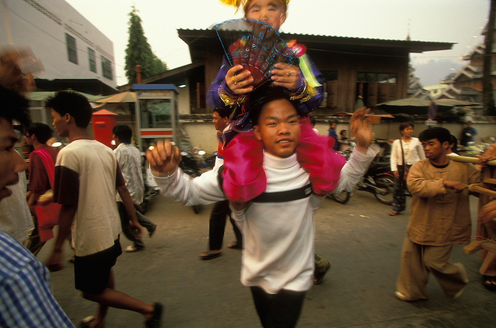Attendant dances with a boy on his shoulders during Poy Sang Long, the yearly ordination of novice monks, Mae Hong Son, Thailand. April 2003. The boy is dressed up as a prince in rememberance of the Buddha.