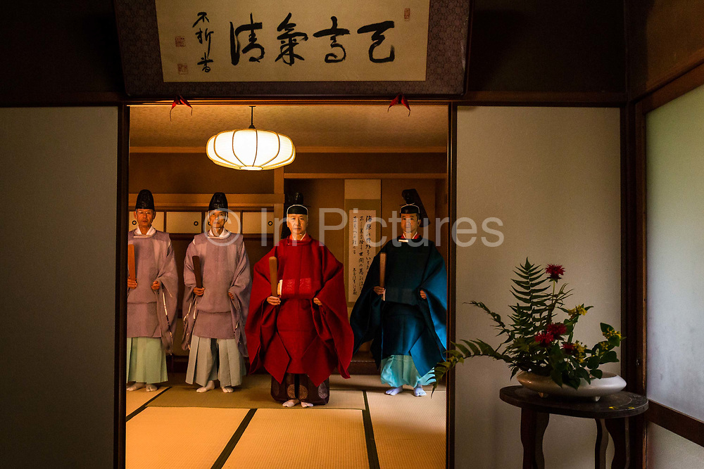 """Shinto priests Masatsugu Okutani, 41 (far right) together with his father Kazufumi Okutani, 71 dressed in their ceremonial clothes in preparation for the Summer Grand Purification ceremony to be held at the Yabuhara Sanctuary. They are the  24th and 25th uninterrupted generational SHINTO priests in their family line dating back to the 12th century AD. Seen here with priests Kagesi Toyama (far left) and Kiyoto Suyama (center left), which will assist in the ceremonial festivities which take place over a 36 hour period in early July every year.  The essence of the ceremony is to remove temporarily all impurities such as rational thought from ones body and mind and maximize one's sensitivities. In other words to be in a state of heightened concentration of the """"here and now"""" and allow one's sensitivities to be replenished as they are a constant source of japanese cultural identity, Kiso Mura village."""