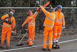 Harefield, UK. 8 February, 2020. HS2 engineers pass a chainsaw to be used for tree felling works for the high-speed rail link over Heras-style fencing on Harvil Road in the Colne Valley.