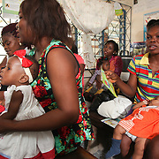 INDIVIDUAL(S) PHOTOGRAPHED: From left to right: Unknown, unknown, unknown, unknown, unknown, unknown, and unknown. LOCATION: Epko Abasi Clinic, Calabar, Cross River, Nigeria. CAPTION: Mothers and their children in the waiting room at the Epko Abasi Clinic, waiting for consultation and treatment.