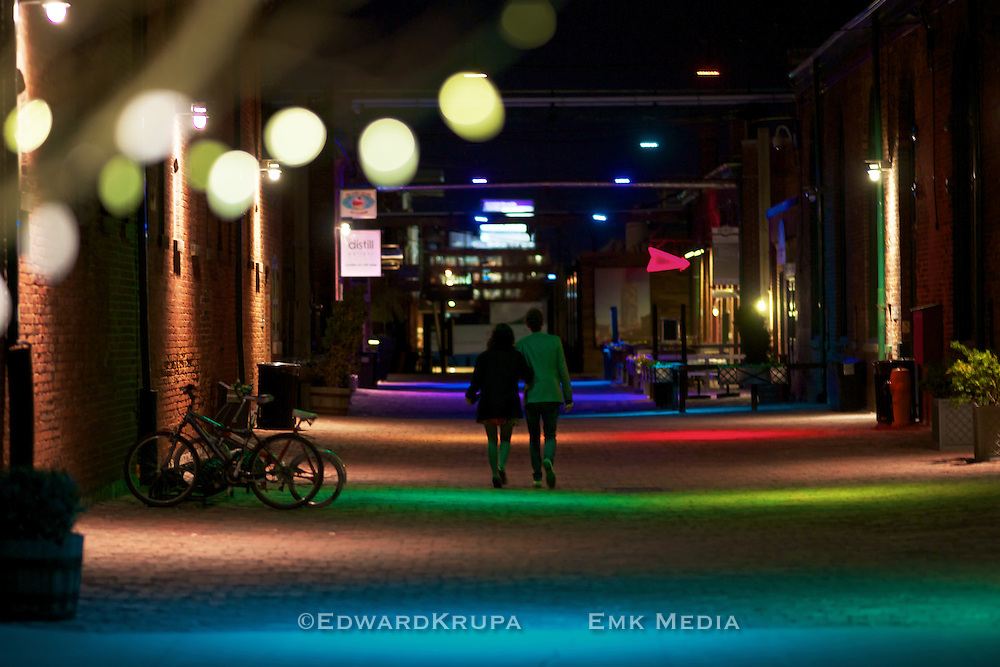 Couple walking along a lane way in Toronto's Distillery District at night.