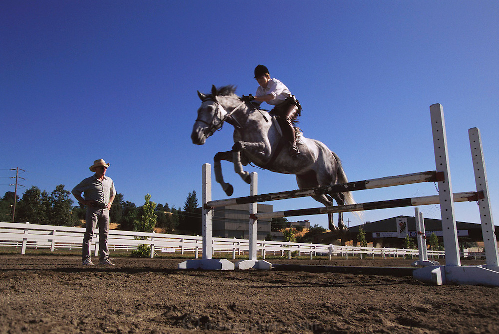 Silicon Valley, California; Deborah Rieman, jumping with trainer at a Stable facility in Portola Valley, California. She was the CEO of an Israeli-founded company Checkpoint, Inc. that became successful designing and selling security firewalls which secure an organization's internal network from external hackers. Model Released (1999).