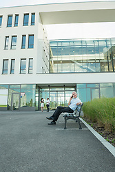 businessman sitting on a bench using his smartphone