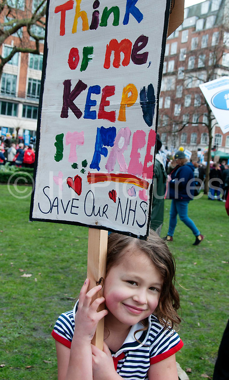 Central London. March 4th 2017 . Tens of thousands of health workers, activists and members of the public protested against austerity and cuts in the NHS National Health Service. A young smiling girl holds a placard she made which says Think of me, keep it free; save our NHS.
