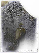 severely eroding glass plate photo with adult man standing by a high wall