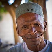 An elder relaxes at the butcher's stall on market day. Near Koumbadiouma in Kolda, Senegal.