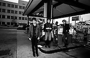 Photo of U2 - The Edge, Larry Mullen, Bono, Adam Clayton at gas station in Atlanta - USA Tour 1981