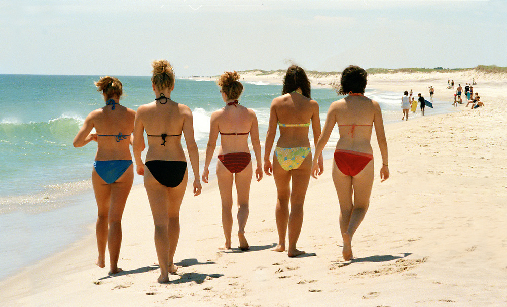 Five women in bikinis walking on the beach in Cape Cod on a summer day