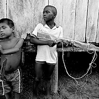 Two young boys playing war with a wooden toy gun. They are some of the countries more than 2 million internally displaced. The jungle area around their village is being fought over by both leftwing rebel groups and rightwing paramilitaries. The inhabitants of many villages have fled to Bellavista. This town was the site of a massacre in May 2002 when a homemade mortar fired by FARC rebels exploded on the roof of a church and killed 119 civillians hiding inside.
