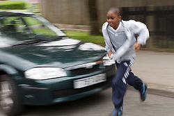 Boy running out into the road in front of a moving vehicle,