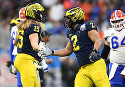 Michigan Wolverines defensive lineman Carlo Kemp (2) and Michigan Wolverines fullback Peter Bush (15) congratulate each other after a staff of the Florida Gators during the Chick-fil-A Bowl Game at  the Mercedes-Benz Stadium, Saturday, December 29, 2018, in Atlanta. ( AJ Reynolds via Abell Images for Chick-fil-A Kickoff)