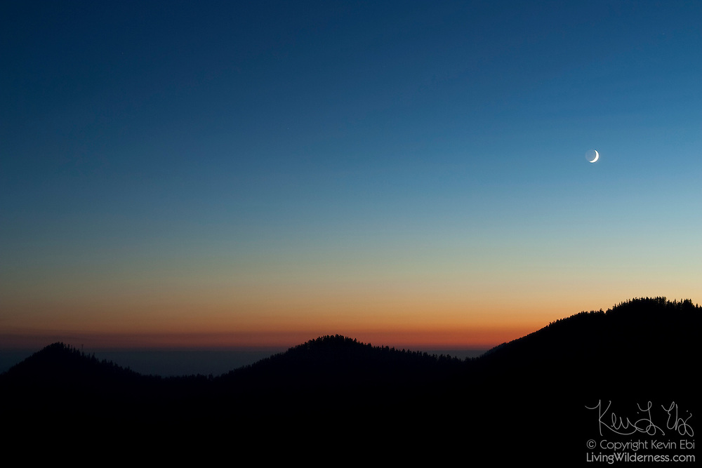 The crescent moon sets over three hills visible from the Wonderland Trail in Mount Rainier National Park, Washington.