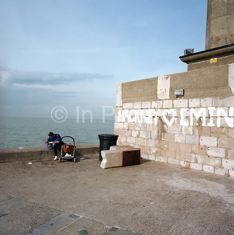 With a calm sea behind, a father cares to his child at the end of the harbour at Margate, the hometown of Britpop artist Tracy Emin, whose name appears in paint on the wall. The man rummages in a baby bag as a child is in the buggy, near the edge of the harbour wall at this southern England resort in the county of Kent. On the right is a reference to the London borough of Hackney loving Emin, the successful artist - a local hero and influential creator of constroversial artworks.