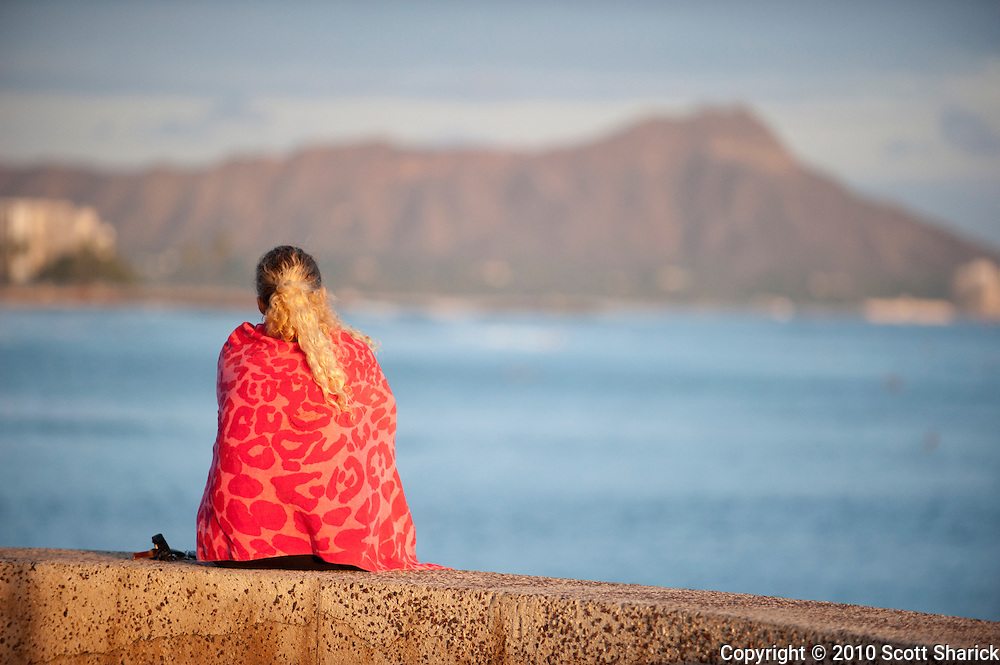 A woman with a red towel sits at Point Panic with Diamond Head in the background.