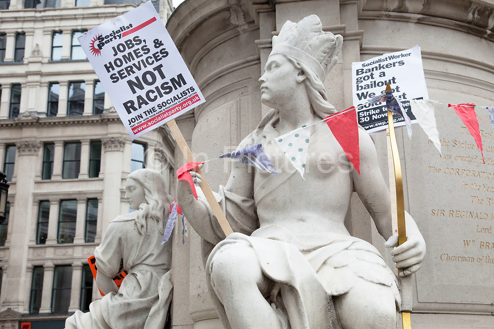 """Statues used as protesters holding placards. Occupy London protest at St Pauls, October 16th 2011. Protest spreads from the US with this demonstrations in London and other cities worldwide. The 'Occupy' movement is spreading via social media. After four weeks of focus on the Wall Street protest, the campaign against the global banking industry started in the UK this weekend, with the biggest event aiming to """"occupy"""" the London Stock Exchange. The protests have been organised on social media pages that between them have picked up more than 15,000 followers. Campaigners gathered outside  at midday before marching the short distance to Paternoster Square, home of the Stock Exchange and other banks.It is one of a series of events planned around the UK as part of a global day of action, with 800-plus protests promised so far worldwide.Paternoster Square is a private development, giving police more powers to not allow protesters or activists inside."""