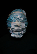 Self portrait wearing a mask from each night shift I worked at Amazon during the intial COVID 19 pandemic.