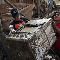 Two men retrieve a cooker from the ruins of their house in Chamelecón, San Pedro Sula, after hurricanes Eta and Iota.<br /> <br /> Hurricanes Eta and Iota hit hard on the north coast of Honduras, leaving some areas flooded for three weeks, destroying people's furniture, belongings, vehicles and houses as well as standing crops.