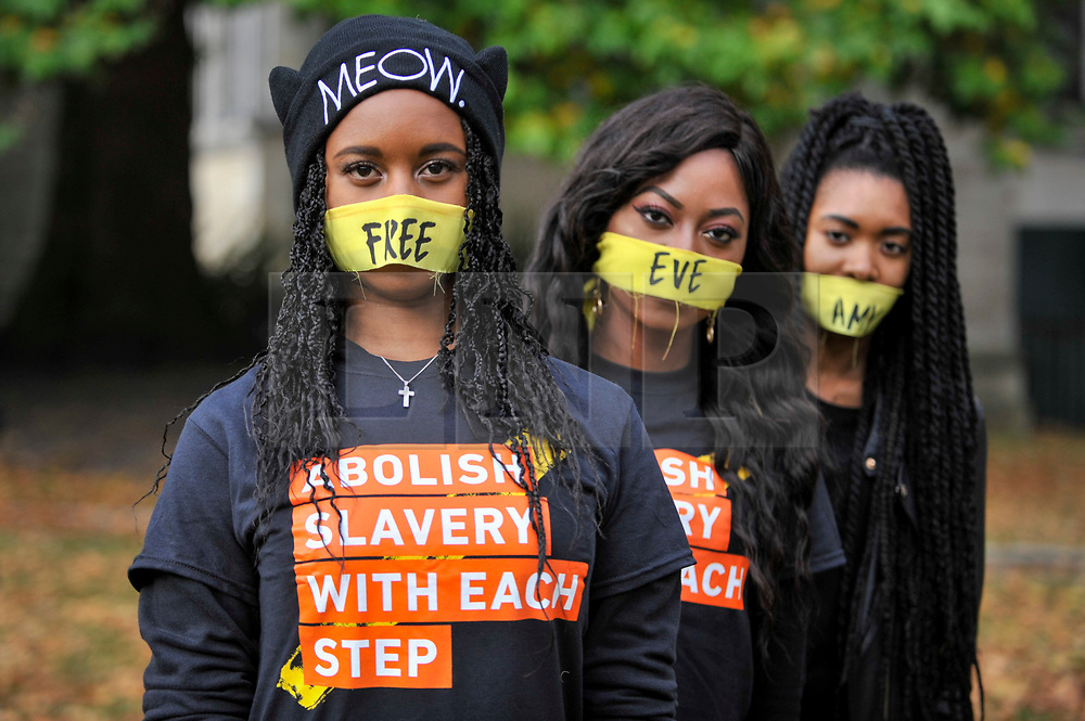 """© Licensed to London News Pictures. 14/10/2107. London, UK. Girls prepare to take part in the """"The Walk For Freedom"""", marching around the capital demonstrating against modern slavery.  The protest is co-ordinated with other walks which abolitionist group A21 is staging in 400 cities around the world on the same day. The facemasks represents the silence of modern slaves. Photo credit : Stephen Chung/LNP"""