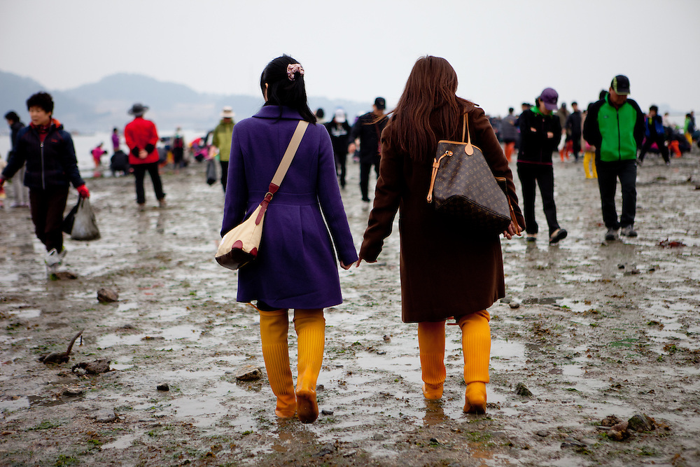 """Well dressed visitors walking the open """"Mysterious Sea Road"""" at Hoedong shore (Jindo island). Jindo is the 3rd biggest island in South Korea located in the South-West end of the country and famous for the """"Mysterious Sea Route"""" or """"Moses Miracle"""". Every spring thousands flock to the shores of Jindo to walk the mysterious route that stretches roughly three kilometers from Hoedong to the distant island of Modo. Materializing from the rise and fall of the tides, the divide can reach as wide as forty meters."""