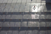 """Seen from an aerial view far above the ground level, is a young boy who leaps across a fountain water feature landscape outside Heathrow Airport's Terminal 5 building .created by the Richard Rogers Partnership (now Rogers Stirk Harbour and Partners). The highlight of a high sun glints off the wet pavement as 55 Choreoswitch waterswitches made by Ocmis are linked to 11 pumps located in a purpose built basement plant room beneath the Plaza. The switches are linked to a unit that also controls the 110 colour changing LED lights integrated into the nozzle housings. Displays can be fast and energetic with dramatic colours or subdued and gentle. From writer Alain de Botton's book project """"A Week at the Airport: A Heathrow Diary"""" (2009). ."""