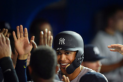 March 29, 2018 - Toronto, ON, U.S. - TORONTO, ON - MARCH 29: New York Yankees Designated hitter Giancarlo Stanton (27) gets congratulated by teammates in the Yankees dugout after his homer in the 9th inning during the MLB season-opener game between the New York Yankees and the Toronto Blue Jays at Rogers Centre in Toronto, ON., Canada March 29, 2018. (Photo by Jeff Chevrier/Icon Sportswire) (Credit Image: © Jeff Chevrier/Icon SMI via ZUMA Press)