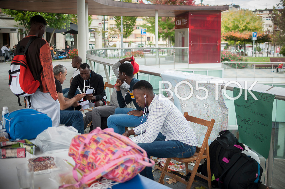 A group of African migrants and volunteers in the main square. Irun (Basque Country). Ocotber 11, 2018. A group of volunteers has created a host network to serve migrants and inform about the public services they are entitled to and the ways to cross the border. This group of volunteers is avoiding a serious humanitarian problem Irun, the Basque municipality on the border with Hendaye. As the number of migrants arriving on the coasts of southern Spain incresead, more and more migrants are heading north to the border city of Irun. French authorities have reacted by conducting random checks as far as the city of Bordeaux, more than 200 kilometers north of the border. Migrants who are caught are then deported back to Irun. (Gari Garaialde / Bostok Photo).