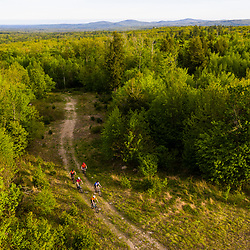 Mountain bikers ride a woods road on new conservation land in New Durham, New Hampshire.