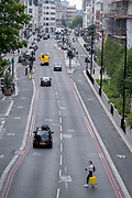 A lone woman carrying a yellow suitcase, crosses the Farringdon Road in the City of London, the capitals financial district, on 24th June 2021, in London, England.