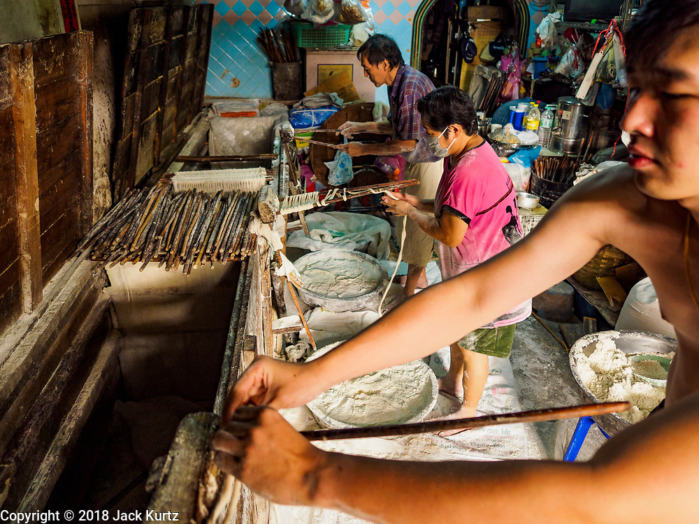 """29 DECEMBER 2018 - BANGKOK, THAILAND: A family makes longevity noodles in their shophouse. The family has been making traditional """"mee sua"""" noodles, also called """"longevity noodles"""" for three generations in their home in central Bangkok. They use a recipe brought to Thailand from China. Longevity noodles are thought to contribute to a long and healthy life and  are served on special occasions, especially Chinese New Year, which is February 4, 2019. These noodles were being made for Chinese New Year.        PHOTO BY JACK KURTZ"""