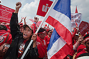 """Mar. 26, 2009 -- BANGKOK, THAILAND: A man carries a Thai flag through a group of anti-government protestors at an opposition rally in Bangkok Thursday. More than 30,000 members of the United Front of Democracy Against Dictatorship (UDD), also known as the """"Red Shirts""""  and their supporters descended on central Bangkok Thursday to protest against and demand the resignation of current Thai Prime Minister Abhisit Vejjajiva and his government. Abhisit was not at Government House Thursday. The protest is a continuation of protests the Red Shirts have been holding across Thailand in March.  Photo by Jack Kurtz"""