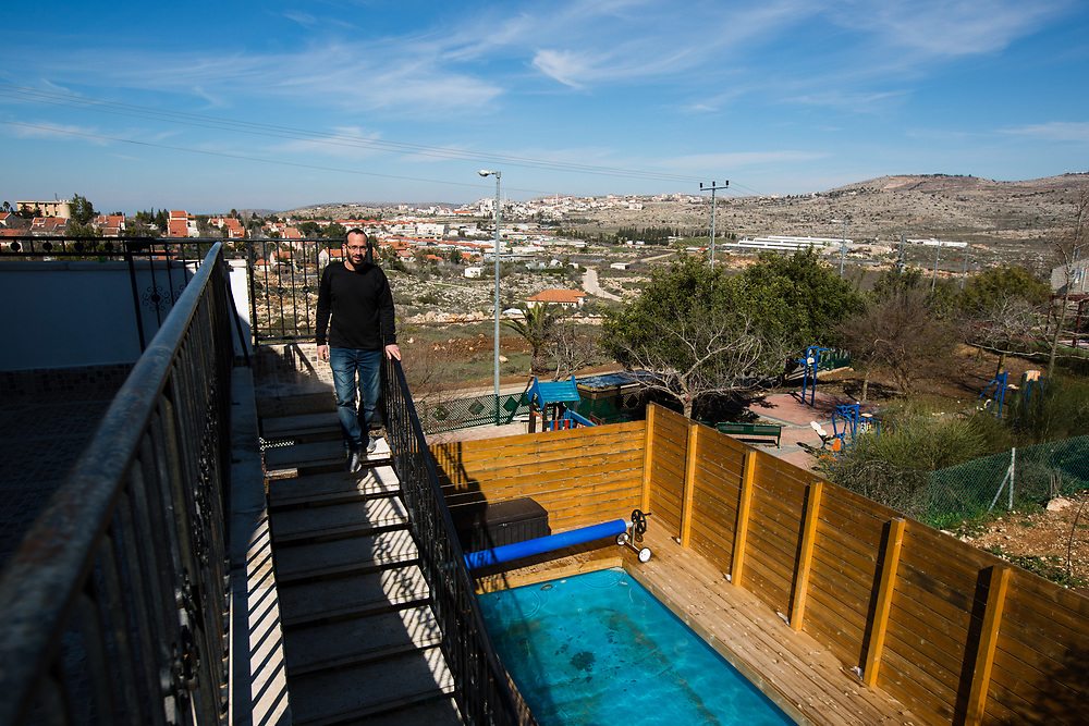 Backdropped by a view of the Jewish settlement of Ofra and the Palestinian village of Silwad (in the background), Yoav Sorek is seen as he walks down a staircase at his bed and breakfast 'Nof Ofra' which is advertised on Airbnb international home-sharing site and rental listings service, in the West Bank Jewish settlement of Ofra, on January 28, 2016.