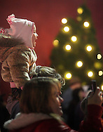 Middletown, NY - A young girl sits on a woman's shoulders to watch Santa Claus light the holiday tree in Festival Square on Nov. 27, 2009.