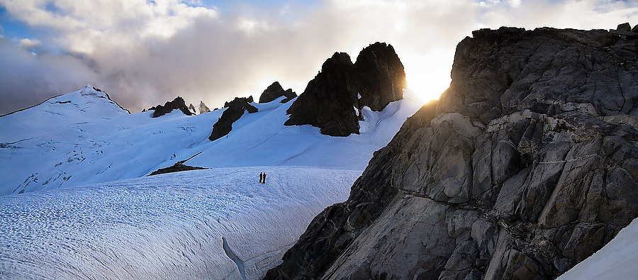 A pair of mountain climbers are dwarfed by the rocky spires and glaciers surrounding them as they stand at Klawatti Col, one of the most scenic climber high camps in North Cascades National Park, Washington.