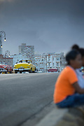 Car on road and people sitting by under storm clouds, Havana, Cuba