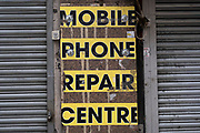 Mobile phone repair centre sign and shutters on 3rd March 2021 in London, United Kingdom.