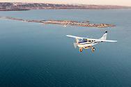 A Homer Air cessna 206 flies past the Homer Spit as it departs Homer, Alaska.