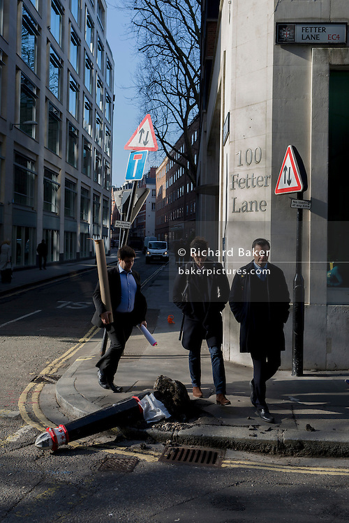 Young men walk past a damaged bollard, knocked over by a vehicle on 13th February 2017, in the City of London, United Kingdom.