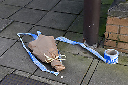 © Licensed to London News Pictures. 20/02/2018. LONDON, UK.  A floral tribute laid by the police cordon.  Police officers and a forensics team attend the scene in Halliday Square, Southall, West London, where a 26 year old man was fatally stabbed on the afternoon of 19 February.  A 39 year old man was arrested at the scene and is in custody.  Investigations are ongoing.  Photo credit: Stephen Chung/LNP