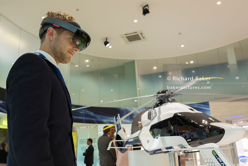 A visitor looks at an interactive augmented reality scale model of the Airbus H160 helicopter in the company's hospitality chalet at the Farnborough Airshow, on 18th July 2018, in Farnborough, England. The Airbus Helicopters H160 (formerly X4) is a medium utility helicopter being developed by Airbus Helicopters.